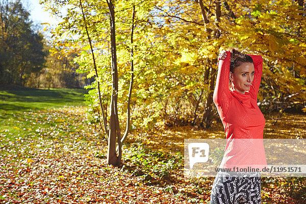 Sportliche Frau in herbstlichem Park