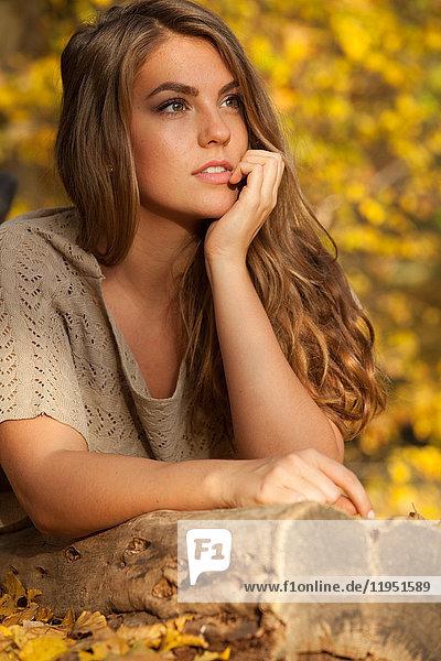 Nachdenkliche junge Frau im Freien im Herbst