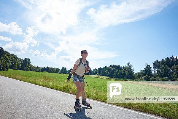 Deutschland  Bayern  Frau fährt Inlineskates auf einer Landstraße