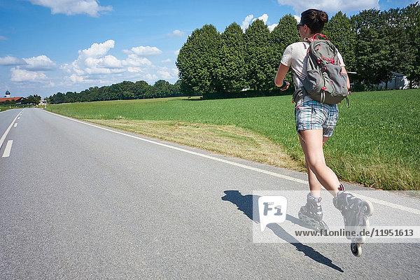 Deutschland  Bayern  Frau beim Inlineskaten auf der Landstraße
