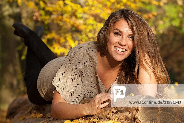 Glückliche liegende junge Frau im Freien im Herbst