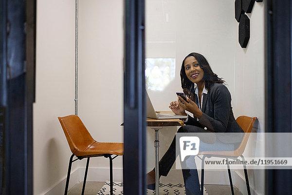 Geschäftsfrau sitzt im Büro  benutzt Laptop  hält Smartphone in der Hand  lächelt