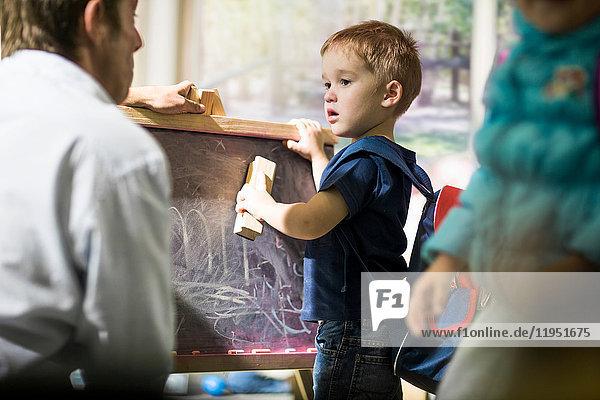 Junge reinigt Tafel mit Staubwedel