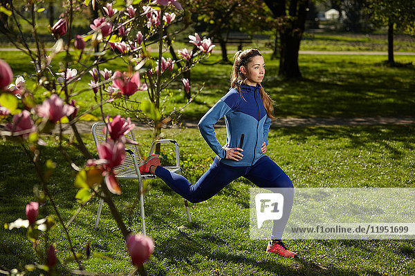 Sportliche Frau beim Stretching im Park im Frühling