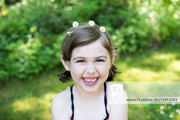 Portrait of young girl outdoors  wearing daisies in hair  smiling