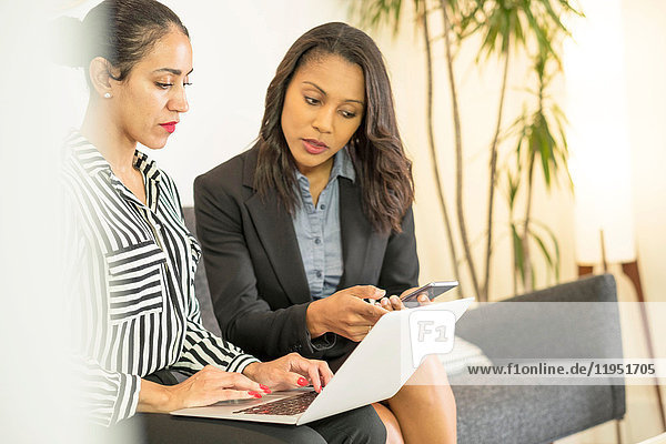 Two businesswomen sitting on office sofa  using laptop  looking at screen