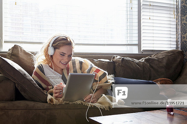 Woman using digital tablet on sofa