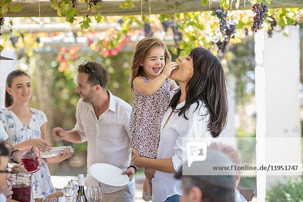 Mädchen füttert Mutter beim Familienessen im Freien