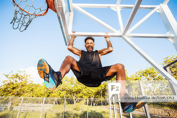 Young man on basketball court  swinging on basketball net frame  low angle view