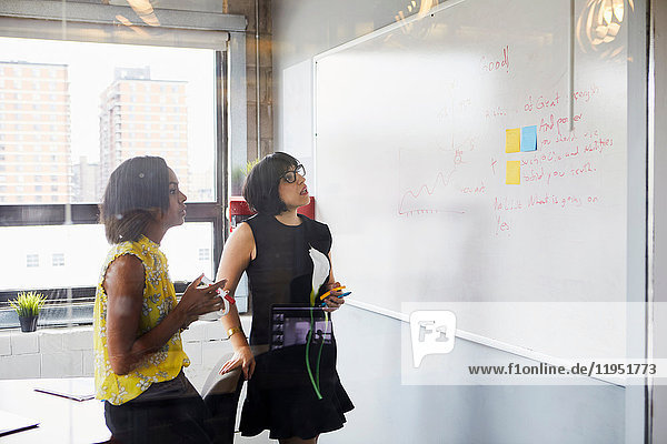 Zwei Frauen im Büro  Problem lösen  Whiteboard benutzen  Haftnotizen auf Whiteboard kleben