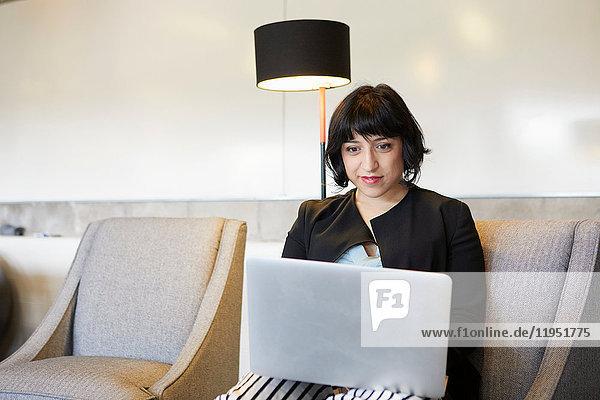 Mittlere erwachsene Frau auf einem Stuhl sitzend  mit Laptop