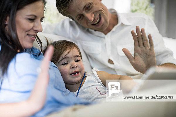Ehemann und Ehefrau benutzen digitales Tablet mit Mädchen auf dem Sofa