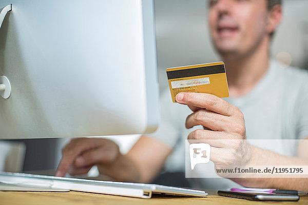 Geschnittene Ansicht eines Mannes  der mit einem Computer eine Kreditkarte hält
