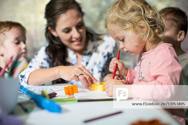 Lehrer und Kinder beim Zeichnen