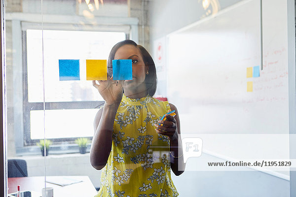 Young woman in office  sticking sticky notes to glass in office