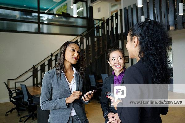Drei Geschäftsfrauen stehen im Amt  im Gespräch