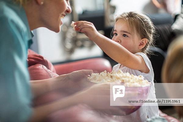 Mädchen  das Mutterpopcorn füttert