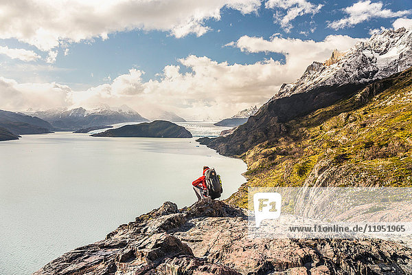 Male hiker crouching to look out over Grey Lake and Glacier  Torres del Paine national park  Chile