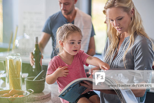 Family in kitchen  mother and daughter looking through book