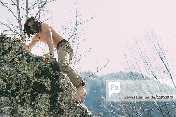Männlicher Kletterboulderer mit nacktem Oberkörper und nacktem Fuss  Lombardei  Italien