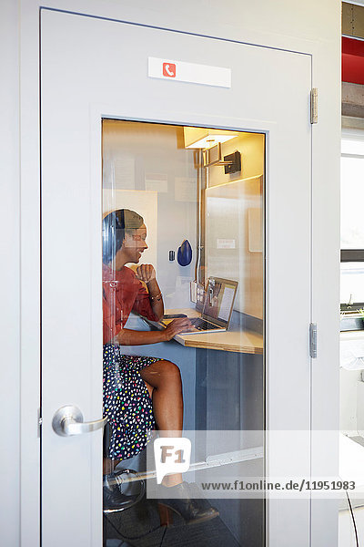 Young woman in office phone booth  using laptop for video call