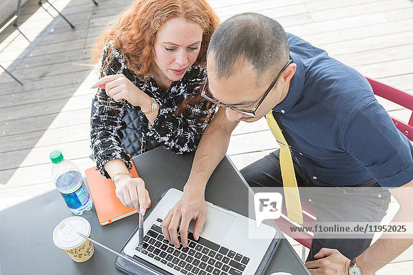 Businessman and woman using laptop at cafe table