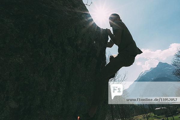 Hinterleuchtete Ansicht eines jungen männlichen Boulderers beim Klettern  Lombardei  Italien