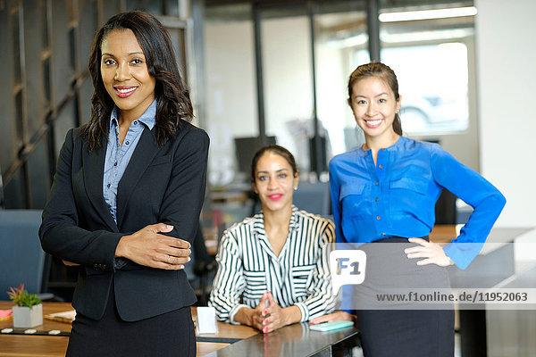 Portrait of three businesswomen in open plan office  smiling