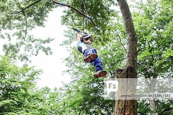 Junge schwingt auf einer selbstgebauten Baumschaukel  niedriger Blickwinkel