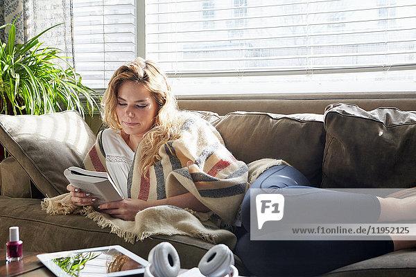 Frau liest Buch auf dem Sofa