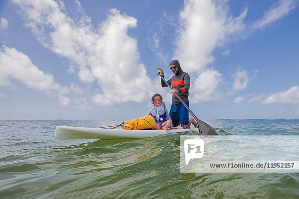 Father and daughter paddle boarding in the Gulf of Mexico  Destin  Florida  USA