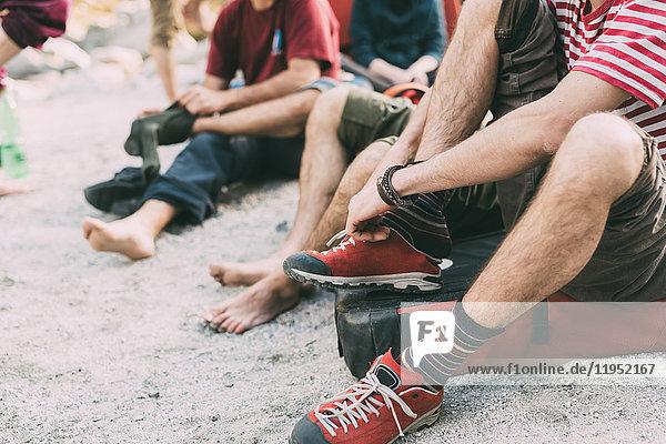 Nackenansicht von erwachsenen Boulderfreunden,  die sich Socken anziehen und Turnschuhe tragen,  Lombardei,  Italien