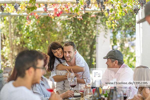 Family having lunch outdoor under grapevine trellis