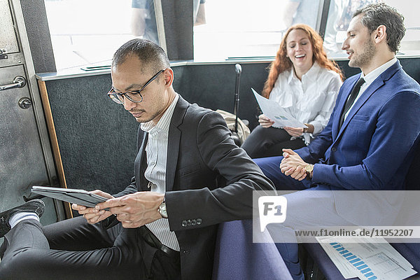 Geschäftsmann betrachtet digitales Tablet auf Passagierfähre
