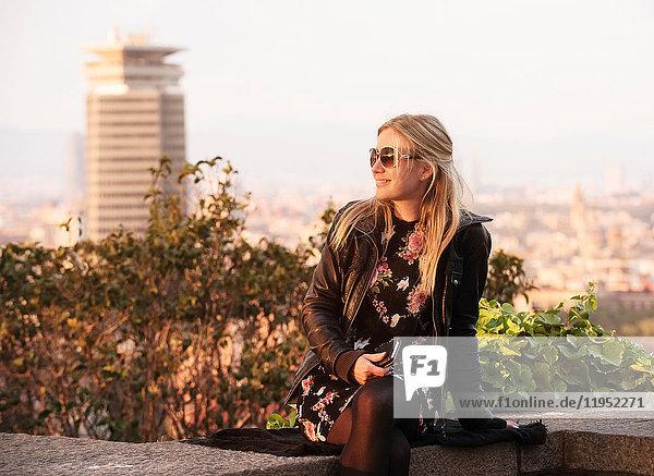 Blondhaarige Touristin sitzt an der Wand  Barcelona  Spanien
