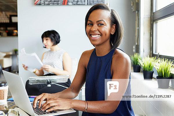 Porträt einer am Schreibtisch sitzenden Frau  die in einem modernen Büro am Laptop arbeitet