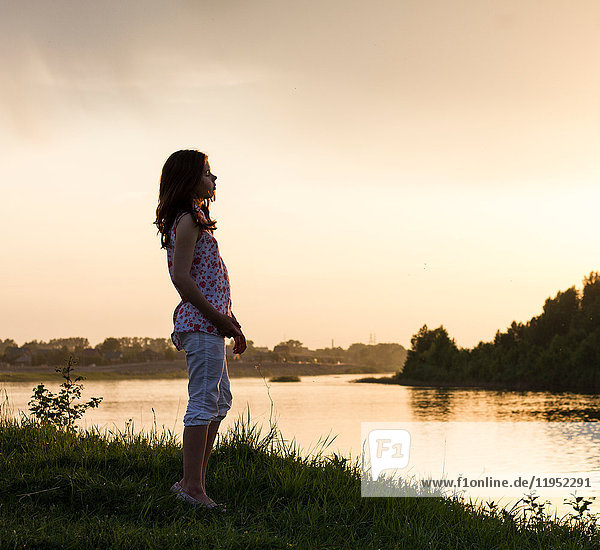 Teenage girl looking out over river at sunset