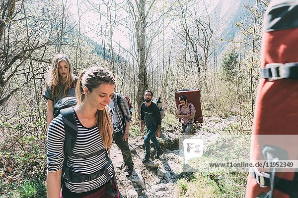 Erwachsene Freunde wandern mit Rucksack und Bouldermatten im Wald  Lombardei  Italien