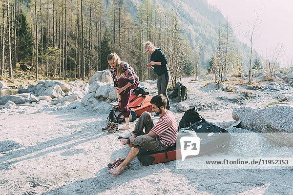 Erwachsene Boulderfreunde ziehen am Flussufer ihre Trainer aus  Lombardei  Italien