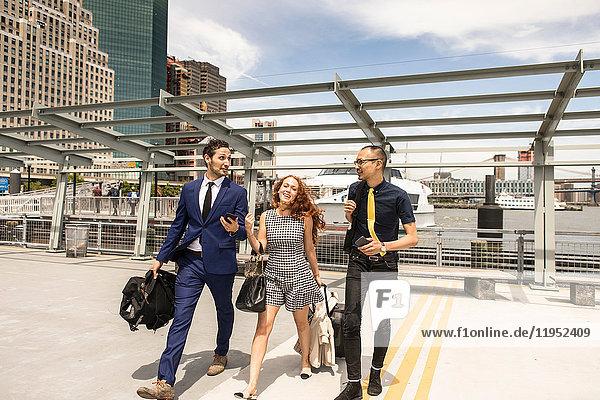Geschäftsleute mit Gepäck beim Gehen und Sprechen am Wasser  New York  USA
