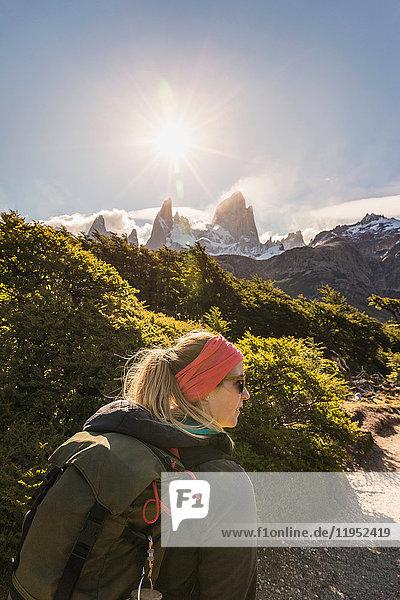 Wanderin beim Wandern in der Nähe des sonnenbeschienenen Fitz-Roy-Gebirges im Los Glaciares-Nationalpark  Patagonien  Argentinien