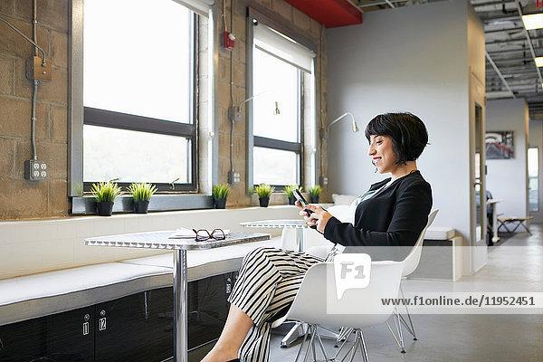 Geschäftsfrau sitzt am Tisch in einer Büroumgebung und schaut auf ein Smartphone