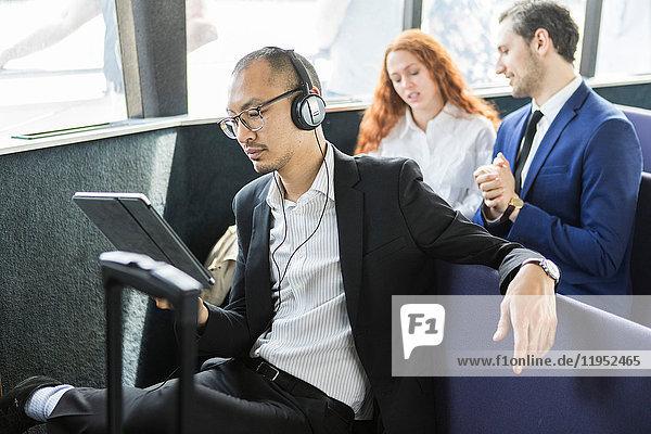Geschäftsmann  der auf der Passagierfähre Kopfhörer hört und auf ein digitales Tablet schaut