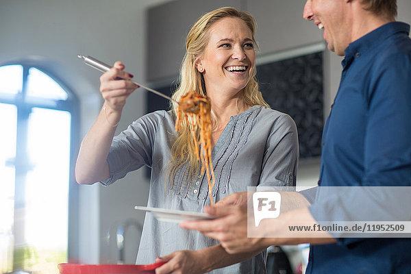 Frau serviert Essen aus Topf  Mann steht neben ihrem Halteteller und lächelt