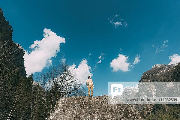 Niedrigwinkelaufnahme eines jungen männlichen Boulderers mit nackter Brust auf dem Gipfel eines Felsblocks  Lombardei  Italien