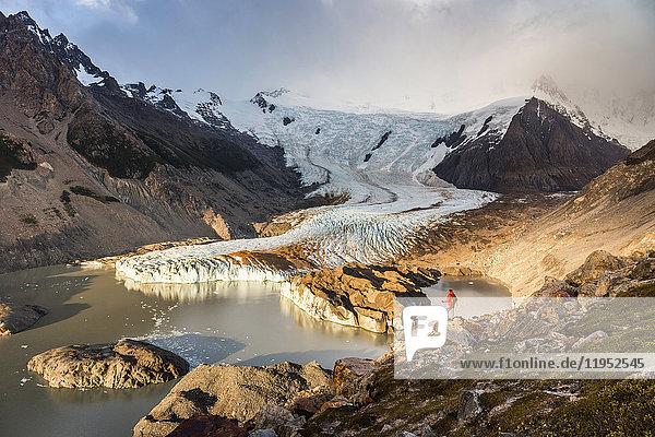 Männlicher Wanderer mit Blick auf den Torre-Gletscher und die Lagune im Los Glaciares-Nationalpark  Patagonien  Argentinien