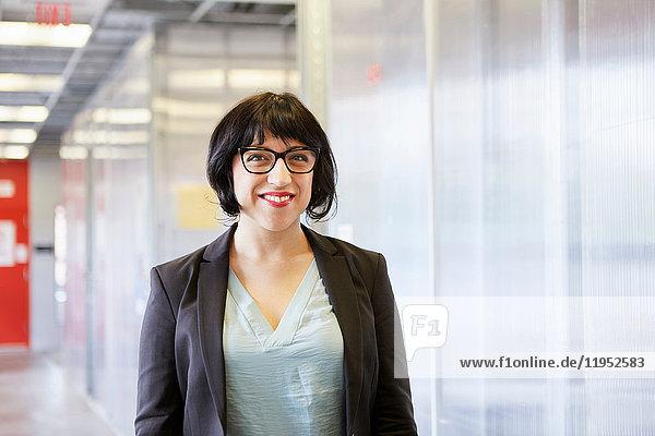 Porträt einer Geschäftsfrau  die im Bürokorridor steht und lächelt