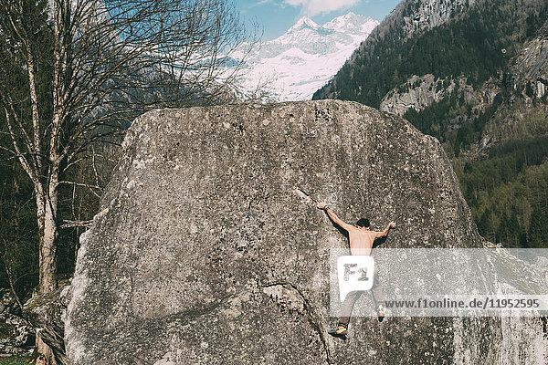 Rückansicht eines jungen männlichen Boulderers beim Bouldern  Lombardei  Italien