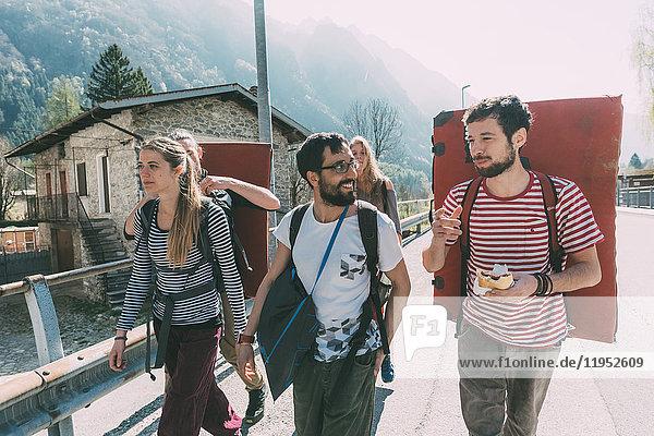 Fünf erwachsene Boulderfreunde gehen über die Brücke  Lombardei  Italien