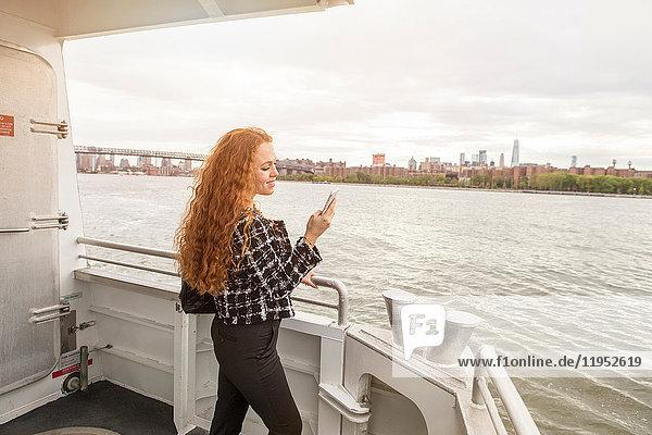 Junge Geschäftsfrau auf dem Fährdeck mit Blick auf Smartphone  New York  USA
